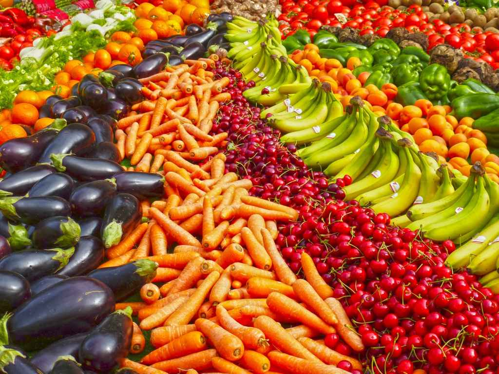 Image of a market stall with vegetables in a rainbow, going from aubergines, to carrots, to cherries, to bananas, to oranges, to green peppers.
