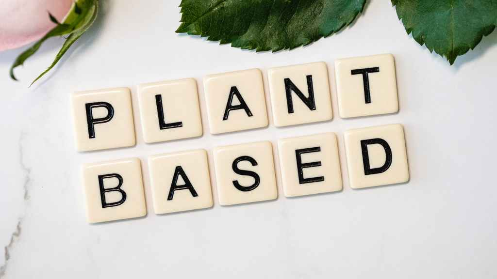 Scrabble style tiles spelling plant based on a white background with some leaves