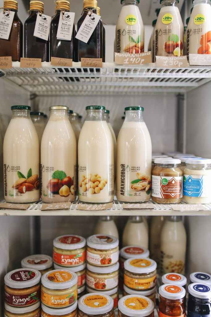 Image of glass bottles of vegan milk in a fridge with labels in a language that I don't understand.